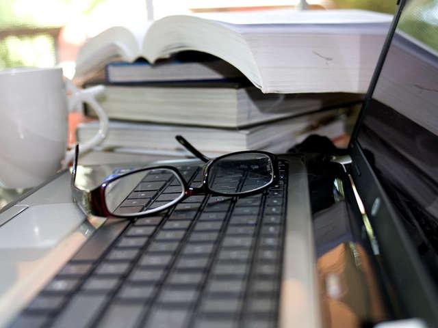 livros-computador-oculos-e-um-copo